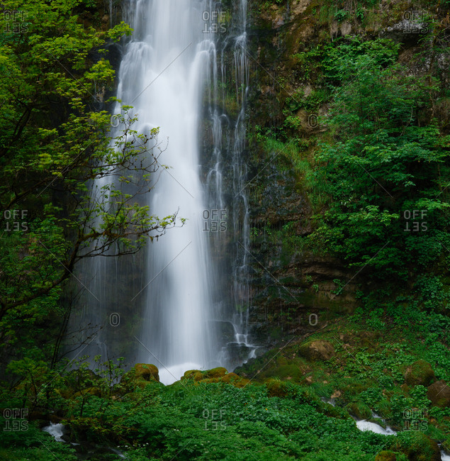 Waterfall cascade in the uplands of the French jura mountains, small tree on the left giving an oriental peaceful zen feeling