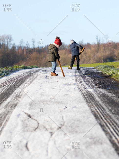Young brother and sister having fun on an icy snowy road writing and drawing with a wooden stick on a sunny cold winter day