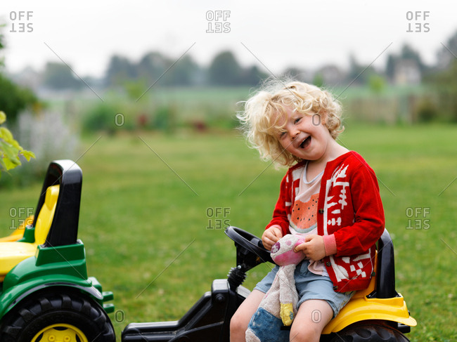 A young girl smiling and having fun in the garden on her tractor toy
