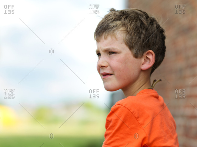 An outdoor portrait of a young boy looking ahead, near a house brick wall on a blurry garden background, green and light blue, short depth of field