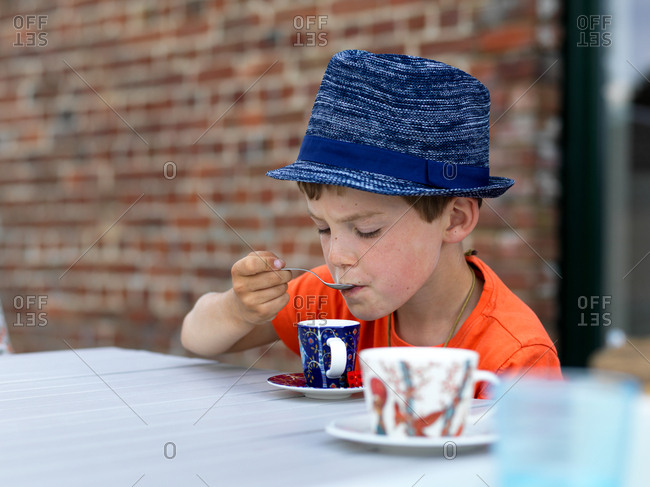 A young boy drinking mint tea in a espresso cup with a small hat