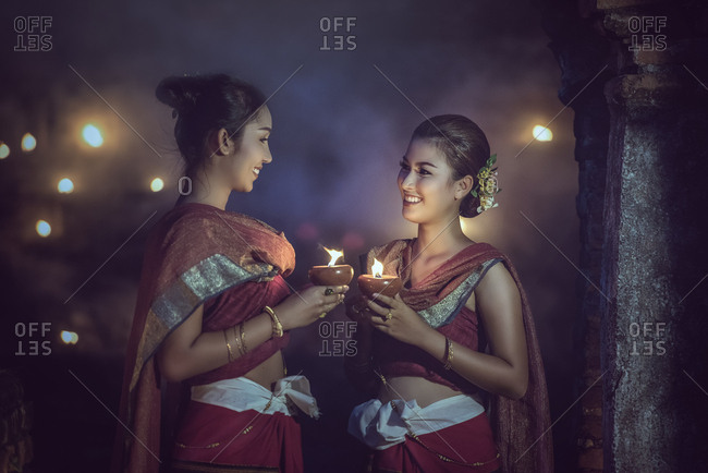 Beautiful Thai girl in Thai traditional costume with candle light