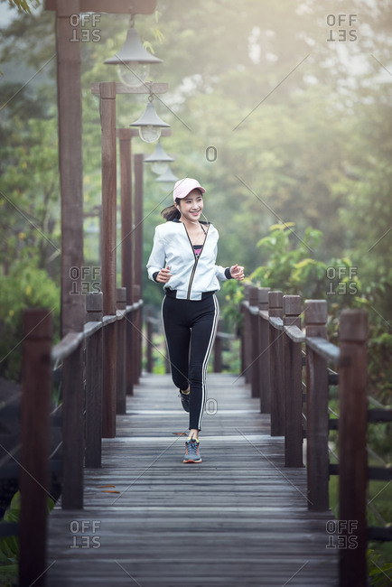 Young fitness sport woman running on the wood bridge in the morning