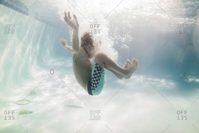 Boy in a pool surrounded by bubbles underwater