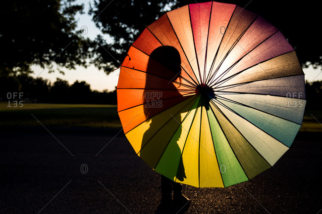 Silhouette of a girl standing behind a multi-colored umbrella at sunset