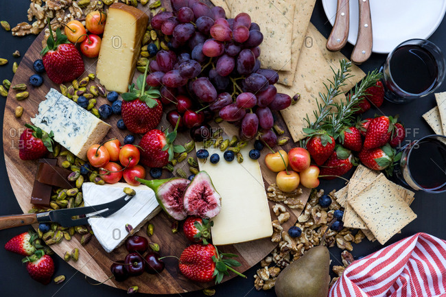 Wooden platter with a variety of cheeses, fruit and crackers