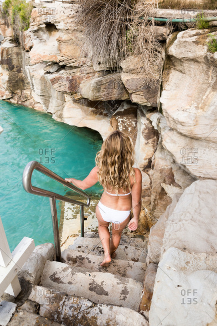 Woman in a bikini walking down stone steps to a natural pool
