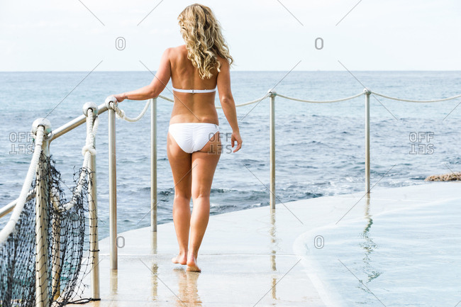 Woman in a white bikini standing on a seaside deck