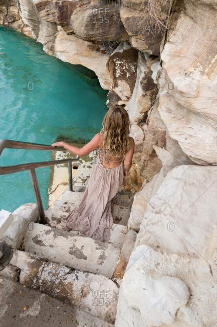 Woman in a backless dress walking down stone steps toward a natural pool
