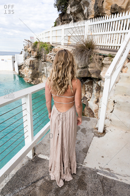 Woman in a backless dress standing on a deck beside the sea