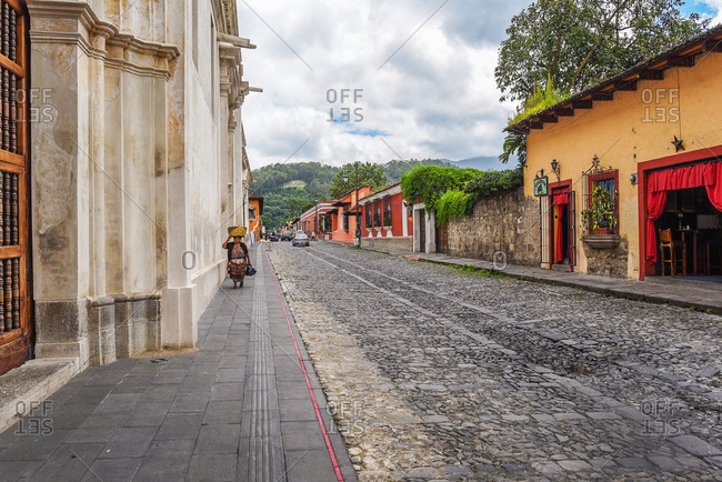Antigua, Guatemala - January 16, 2014: Woman carrying a basket on her head along a cobblestone street