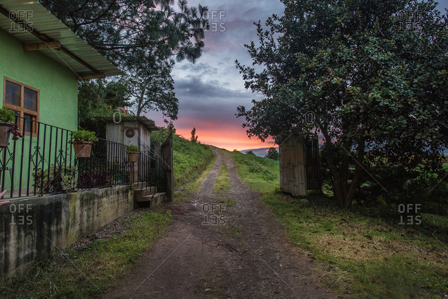 Gate beside a house on a rural dirt road at sunrise