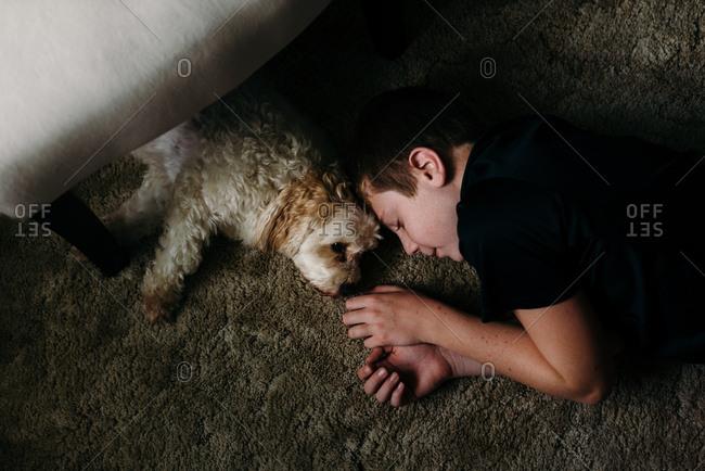 Boy lying on a carpet next to his dog