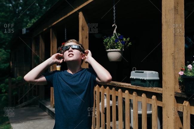 Boy looking toward the sky through solar eclipse glasses