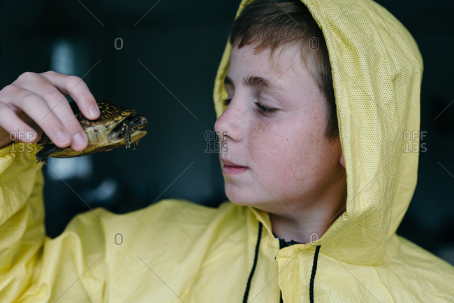 Boy in a yellow jacket holding a turtle in his hand