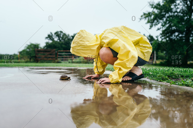 Boy in a yellow raincoat bending down to look at a turtle