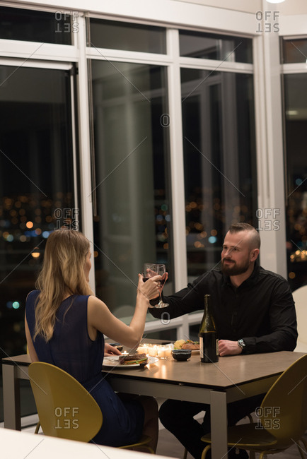 Couple toasting glass of wine while having dinner in living room at home