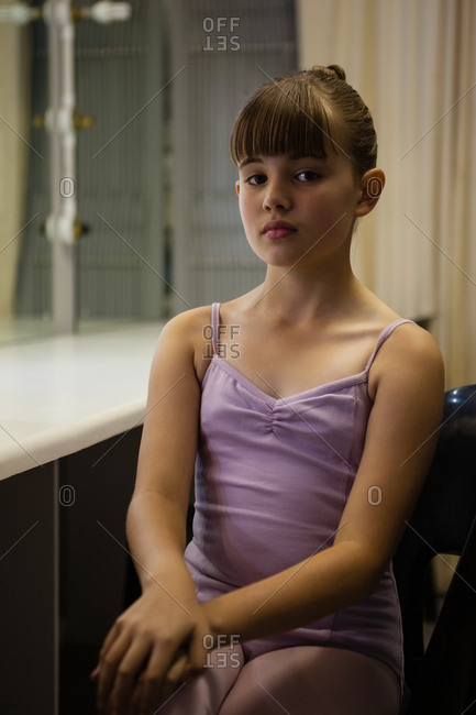 Portrait girl in leotard sitting on chair by mirror