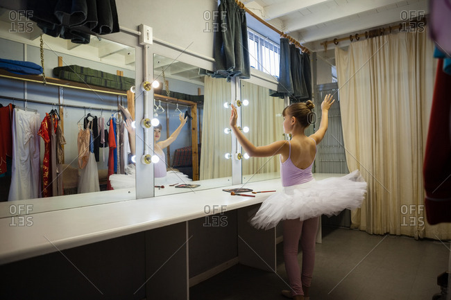 Rear view of girl practicing ballet dance while reflecting on mirror in dressing room at backstage