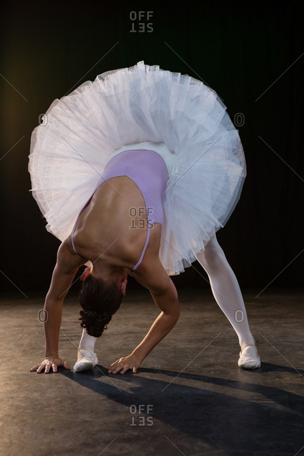 Female ballet dancer stretching before dancing in the studio