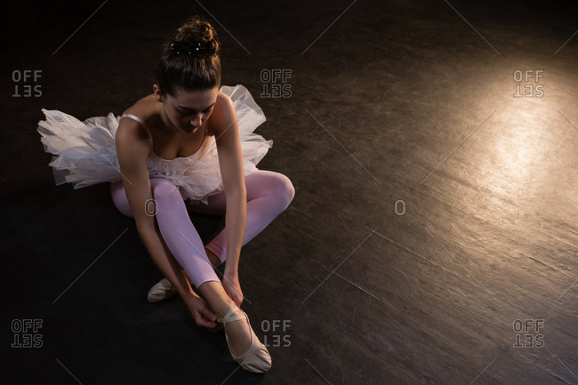 Top view of ballerina tying her shoes
