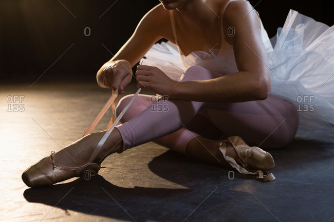 Mid-section of ballerina tying her shoes