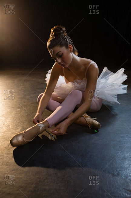 Beautiful ballerina tying her shoes