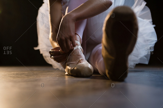 Close-up of ballerina tying her shoes