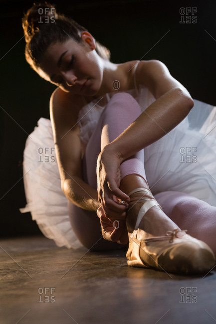 Female ballet dancer tying the ribbon on her ballet shoes in the studio