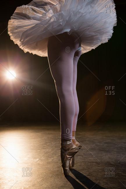 Graceful ballerina standing en pointe in the ballet studio
