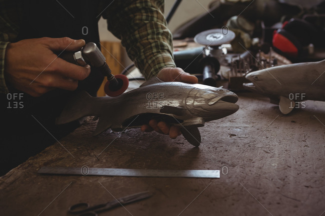 Mid-section of craftsman shaping a metal fish in workshop