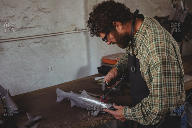 Attentive craftsman shaping a metal fish in workshop