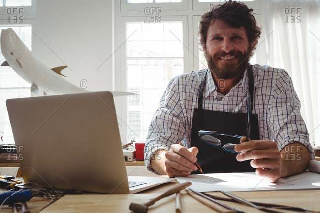 Portrait of happy craftsman working at desk in workshop