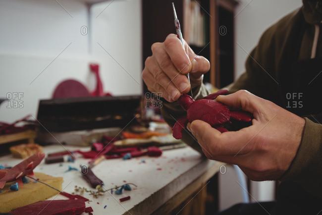 Craftsman working on clay sculpture in workshop