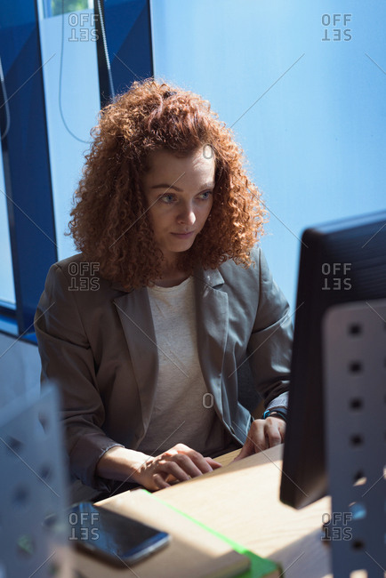 Female student using desktop computer while sitting at desk in classroom