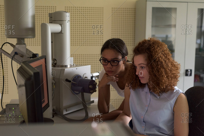 Female students using computer while practicing experiment in lab
