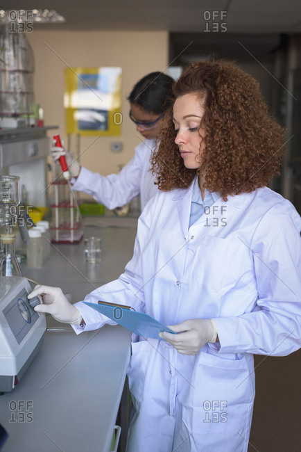 Teenage girls practicing experiment while standing in lab