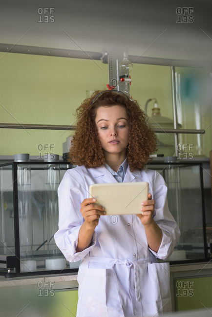 Teenage girl using tablet while standing in lab