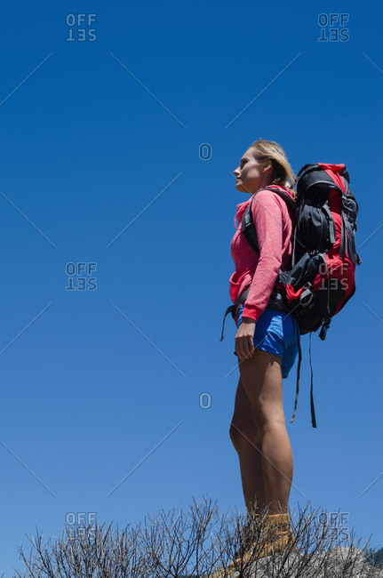 Low angle view of female hiker with backpack standing on rock against clear blue sky