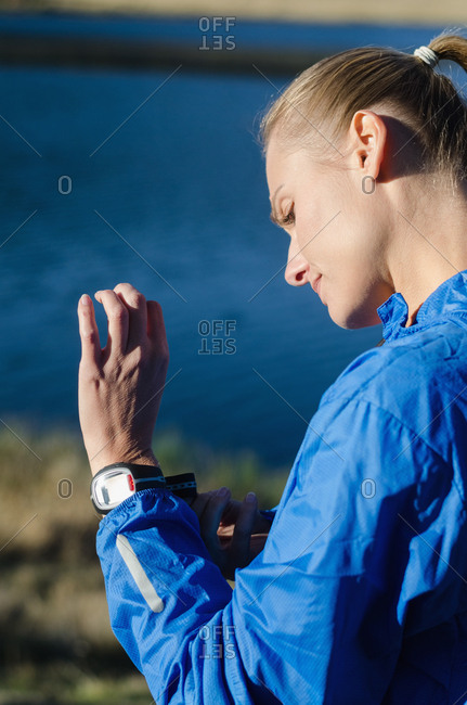 Side view of woman wearing wristwatch while standing against lake