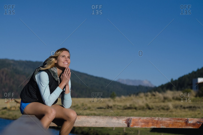 Smiling thoughtful woman sitting on railing against clear blue sky