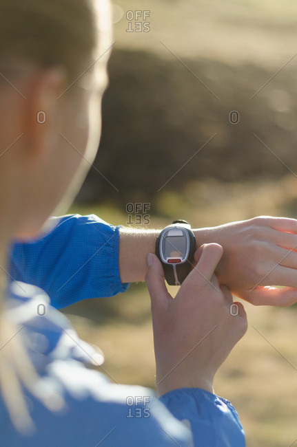 Close up of woman adjusting wrist watch while standing on field