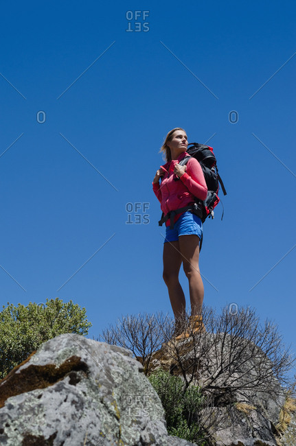 Low angel view of female hiker standing on rock against clear blue sky