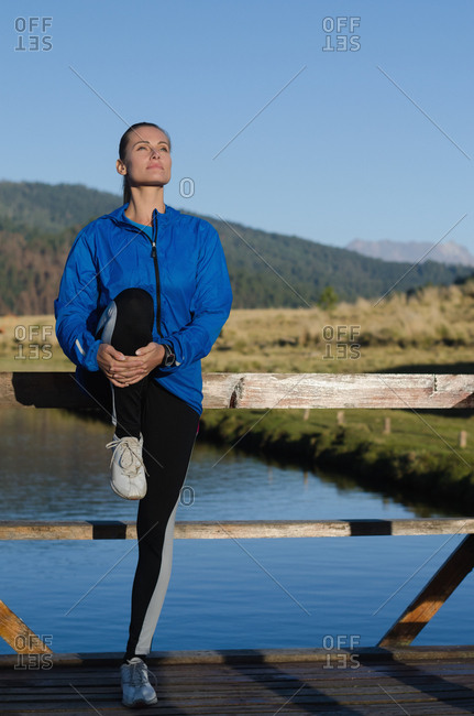 Female athlete stretching while exercising on pier by lake