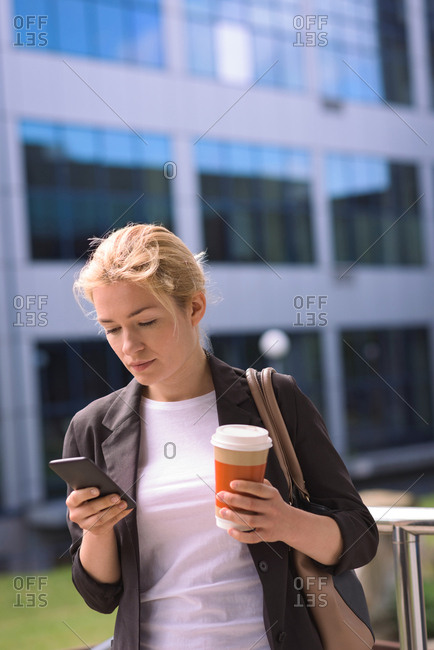University student using mobile phone while having coffee in campus