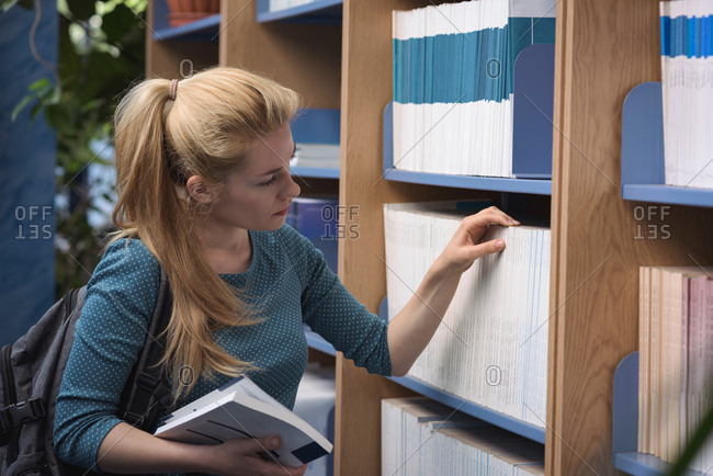 University student selecting book from library in college
