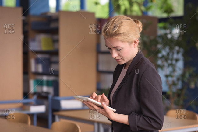University student using digital tablet in classroom at college