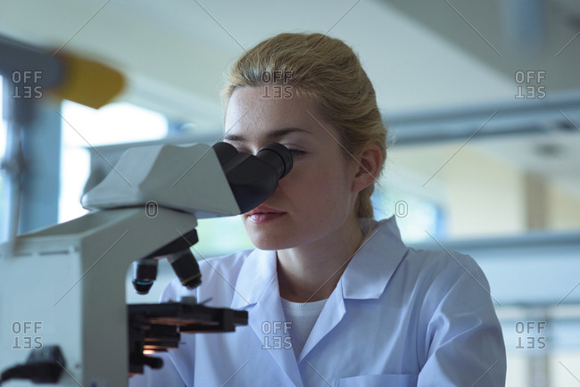 University student doing experiment on microscope in laboratory at college