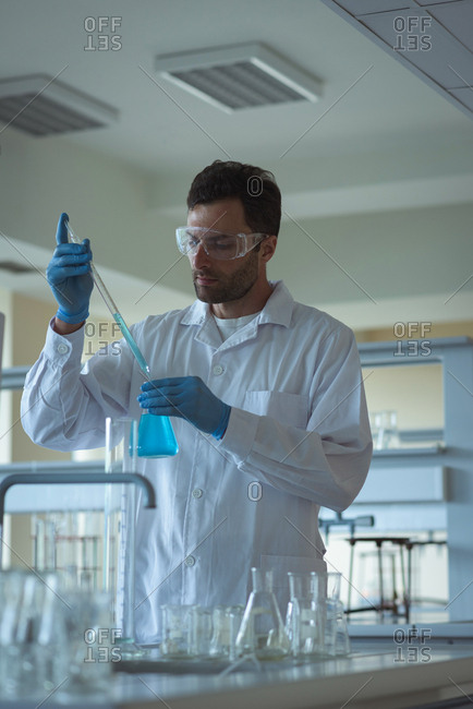 Attentive university student doing a chemical experiment in laboratory