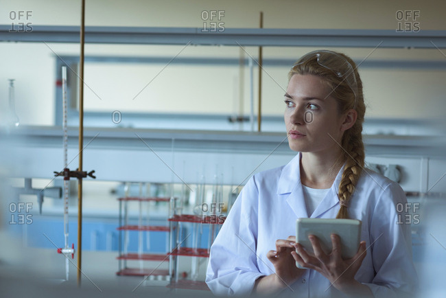 Thoughtful university student using digital tablet in laboratory